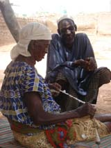 A woman handweaving and chatting